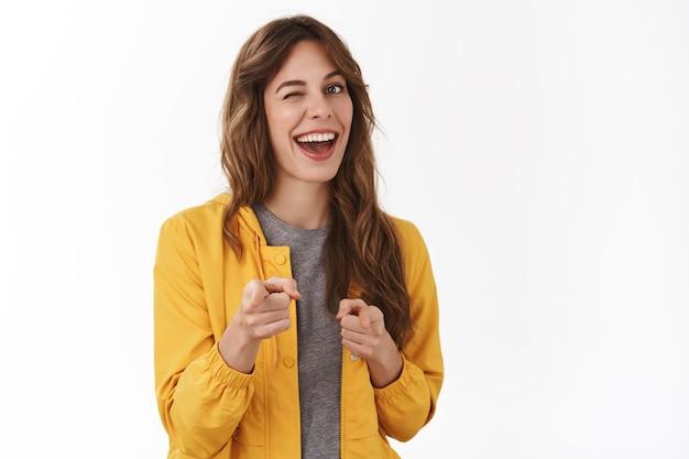 건방진 자신감 있는 편안한 젊은 파티 여성이 앞 손가락 권총을 가리키며 활짝 웃고 있는 당신의 좋은 일 제스처는 훌륭한 선택, 흰 벽을 승인합니다.