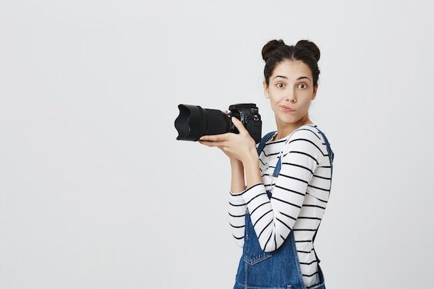 Нахальная милая девушка фотографирует, женщина-фотограф или папарацци с камерой