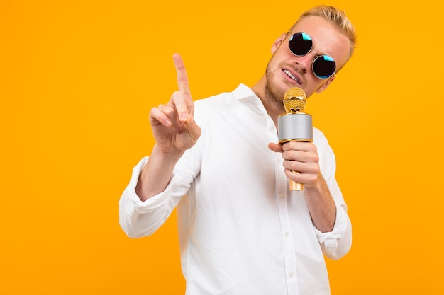 Cheeky european man in a white shirt speaks into microphone on a yellow background.