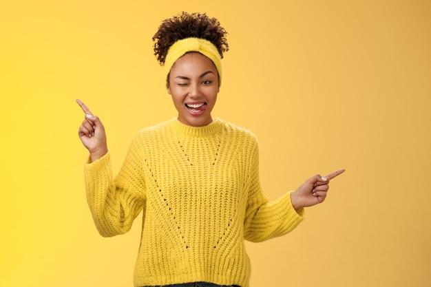 生意気な軽薄な格好良い自信を持って若い黒人女性が横向きに右ウインク生意気な笑顔のショーの舌を指し、黄色の背景に立っているクールな新製品を試してみることを示唆しています。