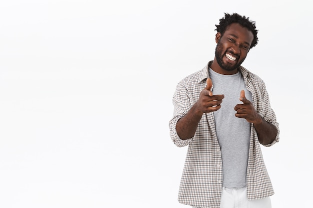 Cheeky and flirty handsome carefree african-american bearded male, wear casual outfit
