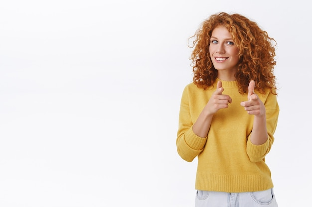 Cheeky, friendly good-looking redhead curly woman in yellow sweater, pointing finger pistols at camera and smiling, picking you, playfully greeting or congratulating person, white wall