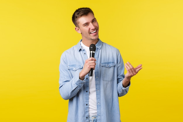 Дерзкий красивый белокурый парень в повседневной одежде выступает с речью, выступает перед аудиторией, поет песни и дерзко улыбается, стоит на желтом фоне, наслаждается караоке ночью и держит микрофон.