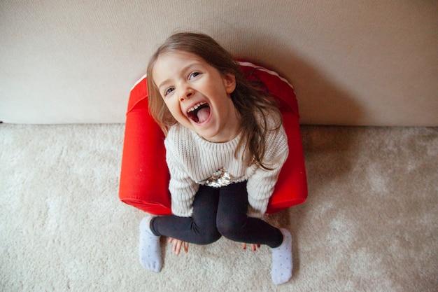Нахальная маленькая девочка играет дома весело