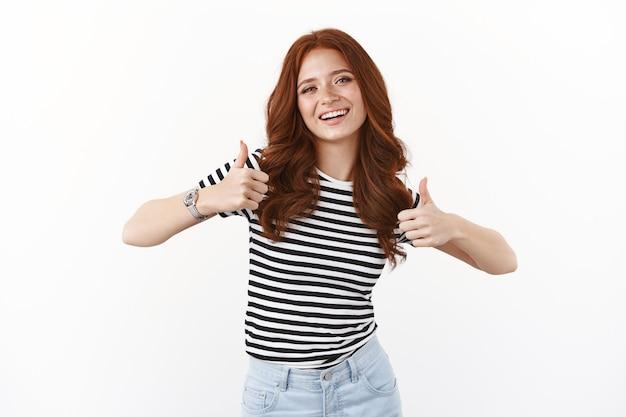 Нахальная хорошенькая рыжая подружка с веснушками в полосатой футболке, показывает одобрительный знак с поднятыми вверх большими пальцами, улыбается и принимает кивок, удовлетворена, дает положительное заключение, как ваш выбор