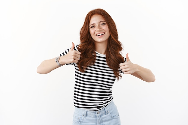 Cheeky pretty redhead girlfriend with freckles in striped t-shirt, show thumbs-up approval sign, smiling and nod acceptingly, satisfied, give positive judgement, like your choice