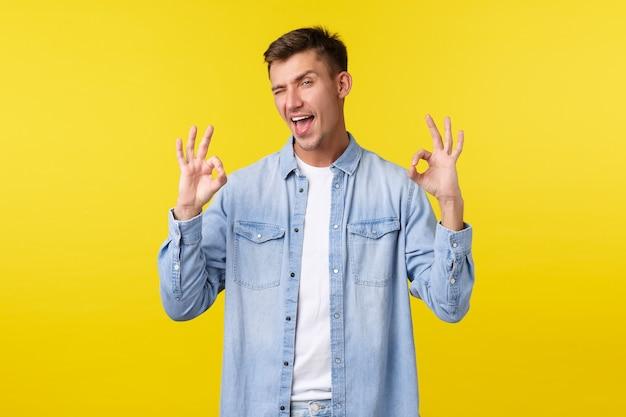 Sfacciato bell'uomo sorridente che mostra la lingua e strizza l'occhio alla telecamera, mostrando gesti ok totalmente soddisfatti, stupito dall'evento, lascia commenti positivi, consiglia servizi o corsi per studenti.