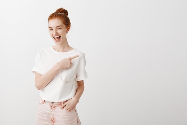 Нахальная улыбающаяся рыжая девушка подмигивает и показывает пальцем вправо