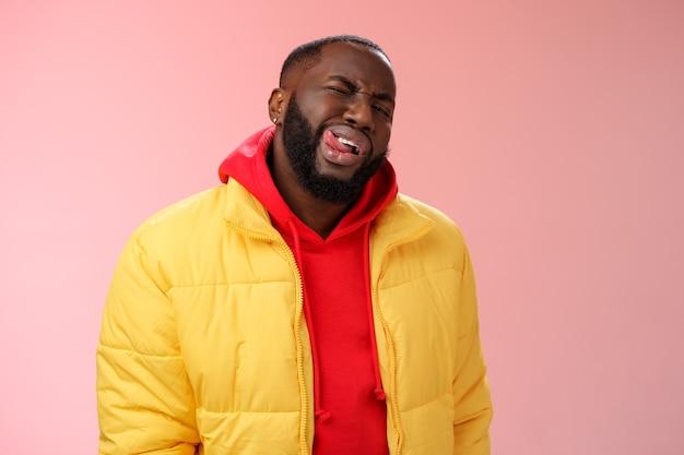 黄色のトレンディなジャケットの赤いパーカーで生意気なスタイリッシュな面白いアフリカのひげを生やした男は、ピンクの背景に立っているマッチョなふりをする女性を印象づけるために舌の生意気な軽薄な視線ウインクカメラを表示します。