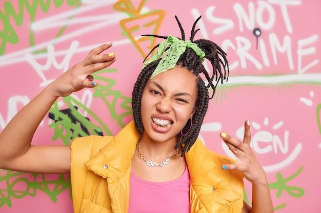 ドレッドヘアを持つ生意気なトレンディな流行に敏感な女の子は、クールなジェスチャーを食いしばって金色の歯をカラフルな落書きの壁にファッショナブルな服のポーズを着させます。