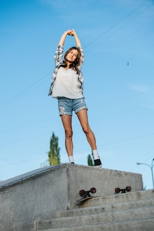 Cheeky woman stretching while standing on concrete parapet against the sky