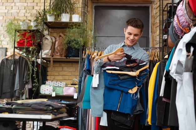 応援服。ハンガーにたくさんの服を持って、笑顔で週末の買い物に満足している陽気な感情的なハンサムな男