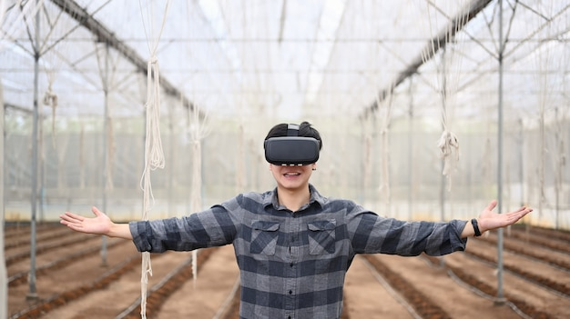 Cheer fun smart farmer wearing visual reality glasses technology while standing in greenhouse.