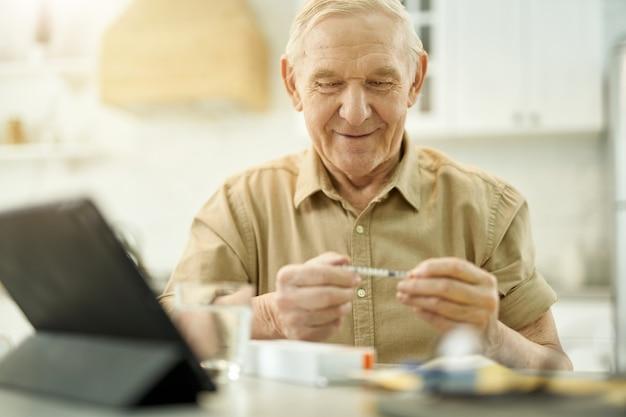 Cheeredup elderly man having a close look at syringe