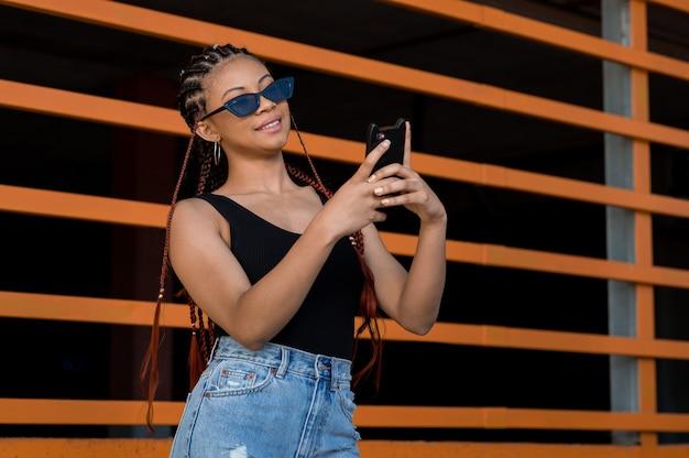 オレンジ色の構造の前で彼女の電話を使用してデッドロックを持つcheerfuアフリカ系アメリカ人の女性