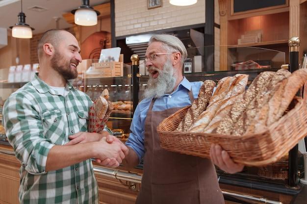 彼の店で焼きたてのパンを購入した後、年配のパン屋と握手するcheerfu男