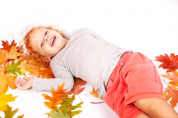 Cheerful 2-3 year old redhead little girl lying on the floor in the studio