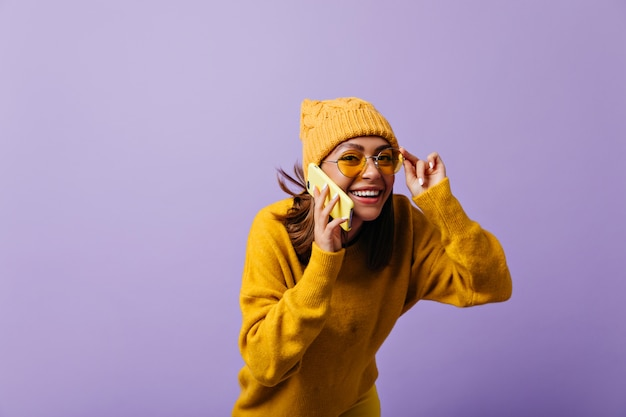 赤褐色の髪の陽気な21歳の女の子は、電話で面白くて面白い会話をしています。肖像画のポーズに興味を持って黄色のサングラスを通して見ている笑う女性