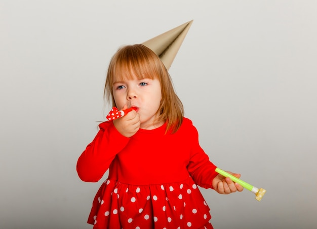 A cheerful 4-year-old girl in a festive hat and a red sweater celebrates her birthday. whistle on white background