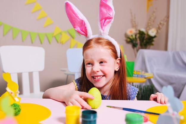 Веселая активная детская девочка с рыжими волосами и ушами кролика рисует яйцо желтой краской