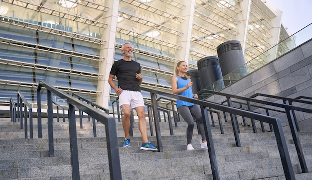 Cheerful active couple man and woman in sportswear having workout together outdoors jogging down