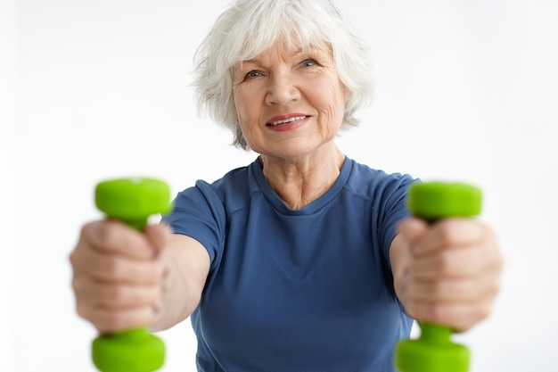 Cheerful active gray haired caucasian female in her sixties gaining strength in gym, training with dumbbells, doing bicep curls, choosing healthy lifestyle. fitness, aging and sports. selective focus