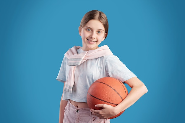 Cheerful active teenage girl in t-shirt holding ball for playing basketball while standing in front of camera against blue background