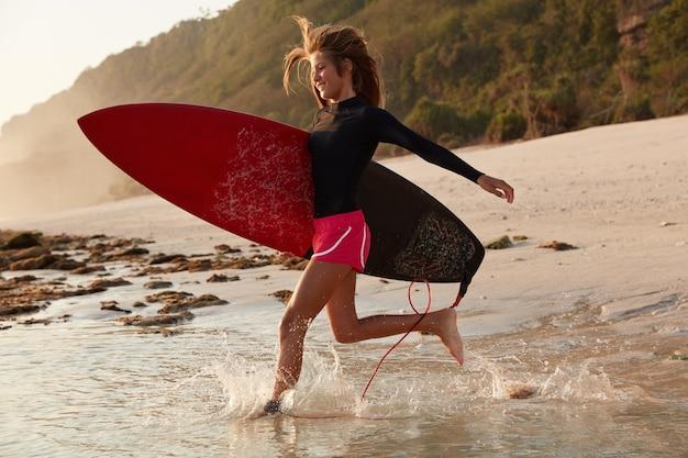 陽気なアクティブな女性が幸せな表情で水にぶつかり、アヒルのダイビングを見せたい