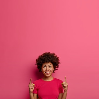 Cheerful adorable curly woman shows something incredible on free space upwards, has happy face expression, wears pink casual t-shirt, poses indoor, proposes service. your promotional content here