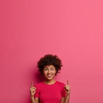 쾌활한 사랑스러운 곱슬 여자는 여유 공간에 놀라운 것을 보여주고 행복한 표정을 지으며 분홍색 캐주얼 티셔츠를 입고 실내 포즈를 취하고 서비스를 제안합니다. 여기에 프로모션 콘텐츠