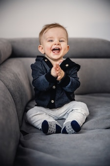 Cheerful adorable laughing little boy clapping with his hands, sitting on sofa.