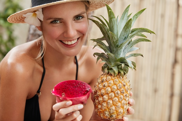 Cheerful adorable woman in straw hat enjoys summer vacation on tropical beach, holds exotic pineapple and dragon fruit