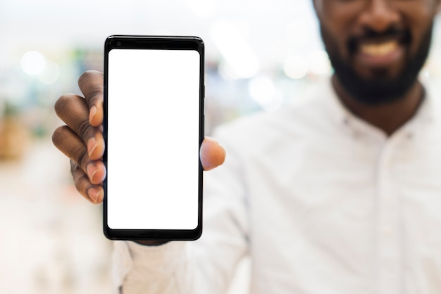 Cheerful adult black male showing mobile phone on blurred background