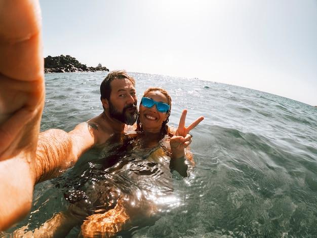 陽気な大人のカップルが海で泳いで夏休みを楽しんで自分撮り写真を撮ります