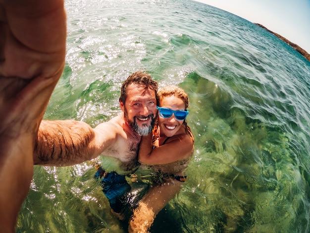 陽気な大人のカップルが海で泳いで夏を楽しんで自分撮り写真を撮ります