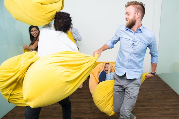 Cheerful adult friends fighting with pillows