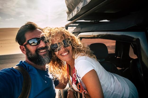陽気な大人の幸せな白人カップルは車で旅行を楽しんだり、友情と関係と一緒に笑顔で自分撮り写真を撮る