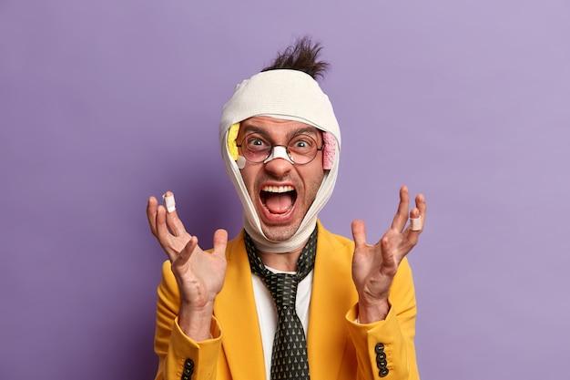 쾌활한 성인 남자는 머리의 외상, 부러진 코 및 눈 밑에 타박상이 있습니다.