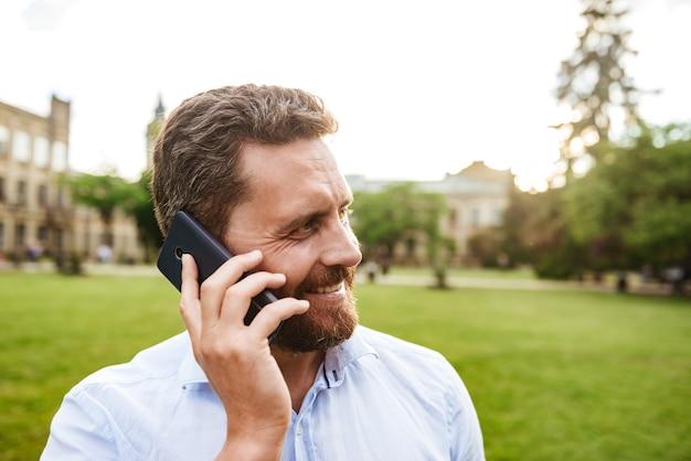 흰 셔츠에 쾌활한 성인 남자, 녹색 공원에서 산책하는 동안 검은 스마트 폰으로 이야기하는 동안 옆으로 찾고