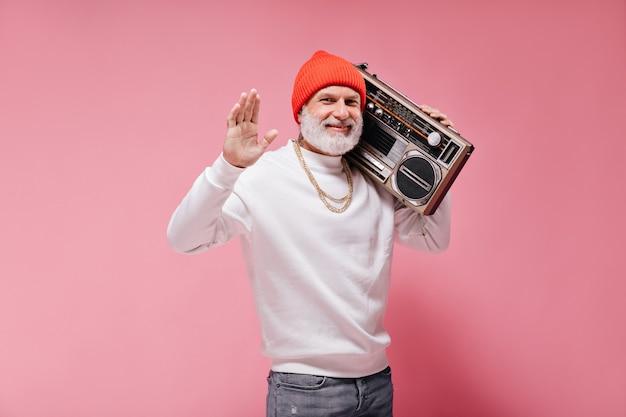 白い流行のセーターとオレンジ色の帽子の陽気な大人の男が手を振って、孤立したピンクの壁にレコードプレーヤーを保持します。