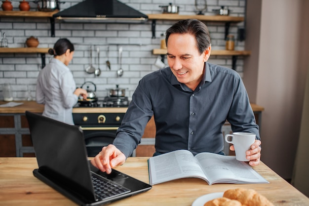 Cheerful adult man sit at table in kitchen.