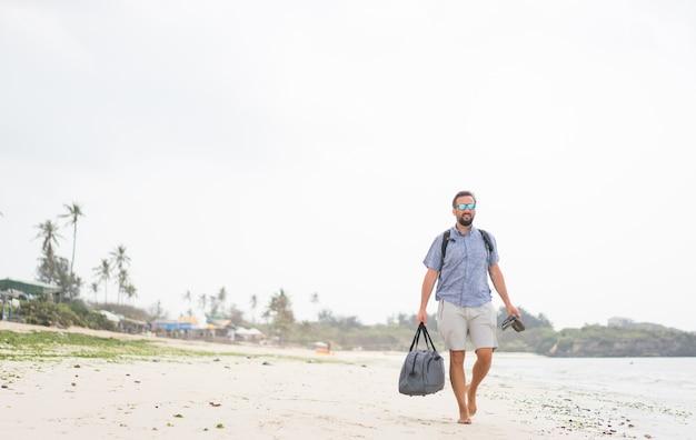 熱帯のビーチで楽しんでいるバッグを持つ陽気な大人の男