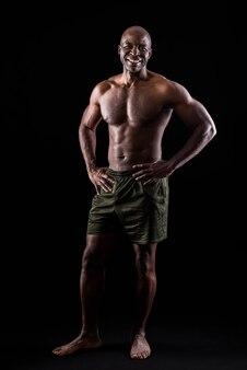 腰に手を当ててカメラを見て立っている陽気な大人の筋肉の男