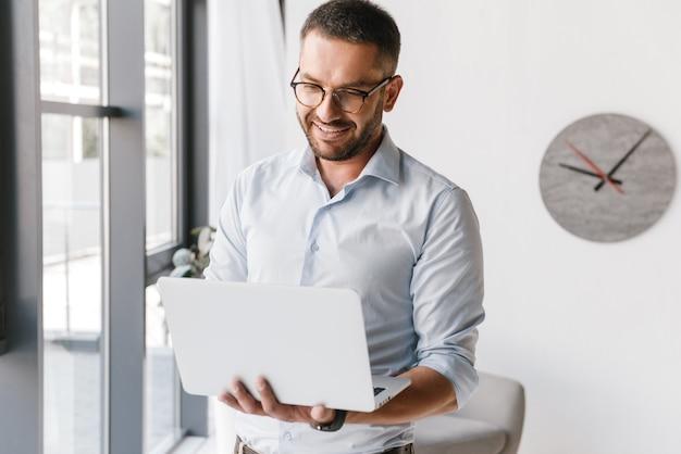 Веселый взрослый офисный мужчина в белой рубашке, выражающий успех, держа серебряный ноутбук во время работы в бизнес-центре