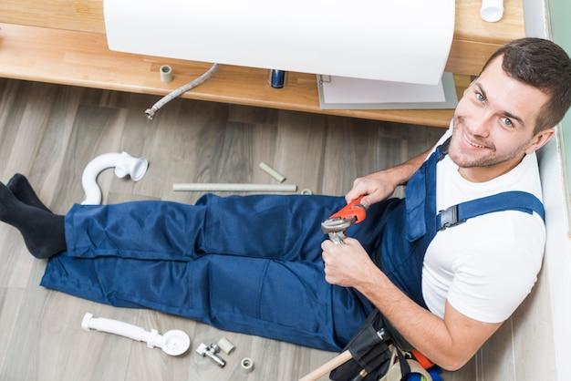 Веселый взрослый водопроводчик, сидящий в ванной комнате