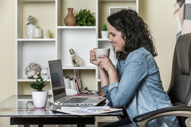 Веселая взрослая женщина пьет ароматный кофе и используя ноутбук дома
