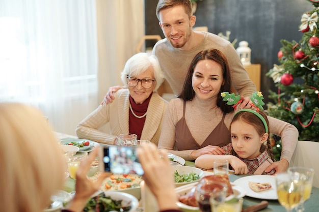 Cheerful affectionate family sitting by served festive table and looking at smartphone in hands of mature woman