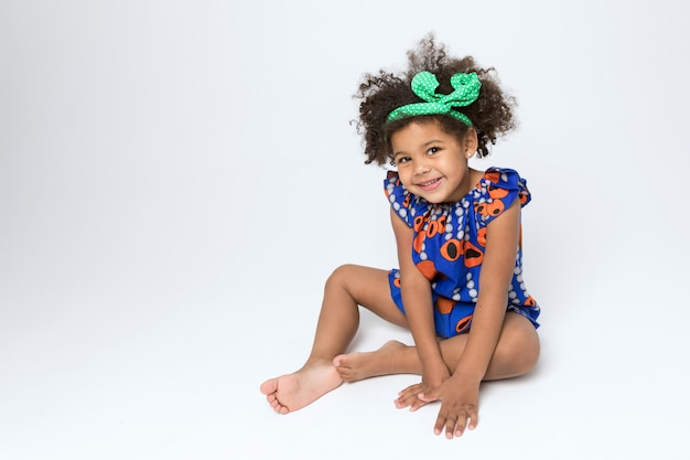 Cheerful african american child in blue and orange colored dress