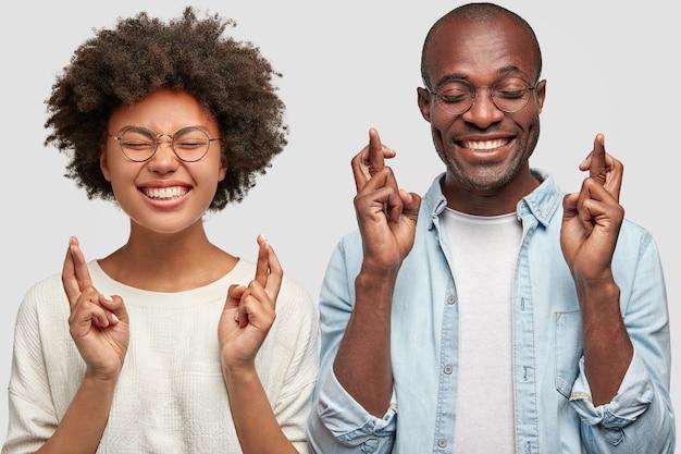 쾌활한 아프리카 계 미국인 부부는 손가락을 교차하고, 넓은 미소를 지으며, 시험 전에 행운을 빕니다. 사람, 민족성 및 신체 언어 개념