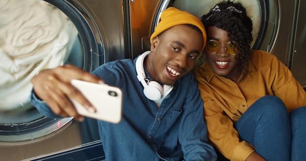 세탁 서비스에서 selfie 사진을 복용하는 동안 스마트 폰 카메라에 웃 고 명랑 아프리카 계 미국인 부부. 행복 한 매력적인 젊은 남자와 여자 공용 세탁실에서 휴대 전화에서 사진을 만드는.